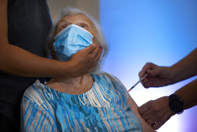 Blossom Koppelman, 86, receives a third Pfizer-BioNTech COVID-19 vaccine from a Magen David Adom national emergency service volunteer, at a private nursing home, in Netanya, Israel, Sunday, Aug. 1, 2021. Israeli health authorities began administering coronavirus booster shots on Friday to people over 60 who've already received both doses of a vaccine, in a bid to combat a recent spike in cases. (AP Photo/Oded Balilty)