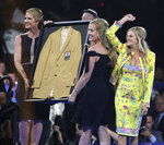 The daughters of Pat Bowlen, a member of the Pro Football Hall of Fame Class of 2019, receive their late father's gold jacket during the gold jacket dinner in Canton, Ohio, Friday, Aug. 2, 2019. (Scott Heckel/The Canton Repository via AP)
