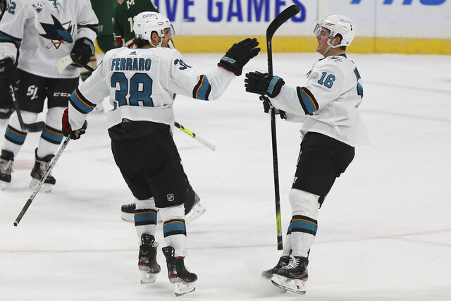 San Jose's Mario Ferraro (38) high fives teammate San Jose's Ryan Donato (16) after Donato scored a goal in the first period of an NHL hockey game against the Minnesota Wild, Sunday, Jan. 24, 2021, in St. Paul, Minn. (AP Photo/Stacy Bengs)