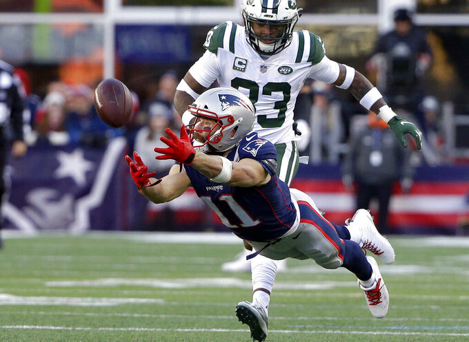 ADDS RETIREMENT ANNOUNCEMENT FILE — In this Sunday, Dec. 30, 2018 file photo New England Patriots wide receiver Julian Edelman (11) stretches but cannot catch a pass in front of New York Jets safety Jamal Adams, rear, during the second half of an NFL football game, in Foxborough, Mass. The Patriots terminated Edelman's contract with a failed physical designation Monday, April 12, 2021, according to the NFL's transaction wire. Citing a knee injury that cut his 2020 season short after just six games, Edelman announced Monday that he is retiring from the NFL after 11 seasons.   (AP Photo/Steven Senne, File)