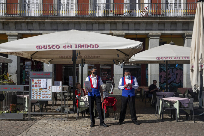 Waiters wearing face masks to prevent the spread of coronavirus wait for customers at the Plaza Mayor square in downtown Madrid, Spain, Friday, Oct. 9, 2020. Spanish Prime Minister Pedro Sánchez is holding a Cabinet meeting to consider declaring a state of emergency for Madrid in order to impose stronger anti-virus restrictions on reluctant regional authorities. (AP Photo/Manu Fernandez)