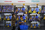 A woman and a child pass Chinese brands of flat screen TVs on display at a hypermarket in Beijing, Wednesday, July 11, 2018. China's government has criticized the latest U.S. threat of a tariff hike as