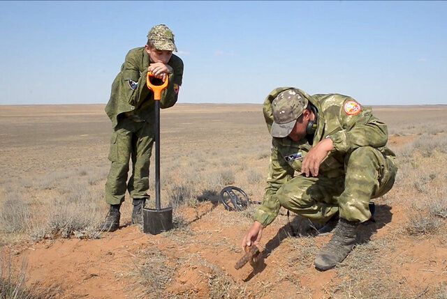 In this May 5, 2020, frame from video, Alfred Abayev, head of a volunteer group searching for remains of the WW II Red Army soldiers, right, looks at projectile left on a WW II battlefield near Khulkhuta in the province of Kalmykia in southern Russia. The search is part of a broad effort by myriad volunteer groups across the country to pay tributes to the fallen WW II soldiers. (AP Photo/Radik Nurmukhamedov)