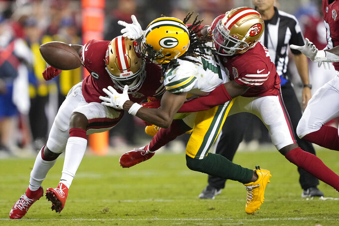 Green Bay Packers wide receiver Davante Adams, middle, cannot catch a pass between San Francisco 49ers cornerback Jimmie Ward, left, and defensive back Emmanuel Moseley during the second half of an NFL football game in Santa Clara, Calif., Sunday, Sept. 26, 2021. (AP Photo/Tony Avelar)