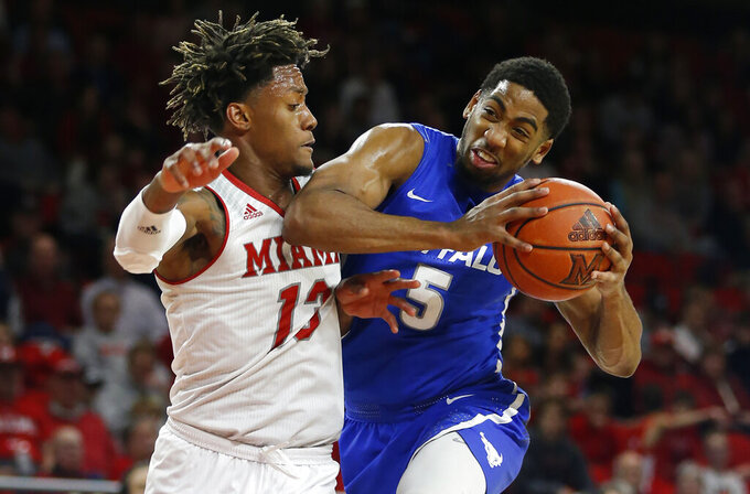 Buffalo guard CJ Massinburg (5) drives to the basket against Miami (Ohio) forward Dalonte Brown (13) during the second half of an NCAA college basketball game, Friday, March 1, 2019, in Oxford, Ohio. Buffalo won 77-69. (AP Photo/Gary Landers)