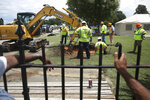 Tameka Colbert and Patrick Cooper watch as researchers do a test excavation at Oaklawn Cemetery in Tulsa, Okla., in the search for possible mass graves from the 1921 Tulsa Race Massacre. (Mike Simons/Tulsa World via AP)