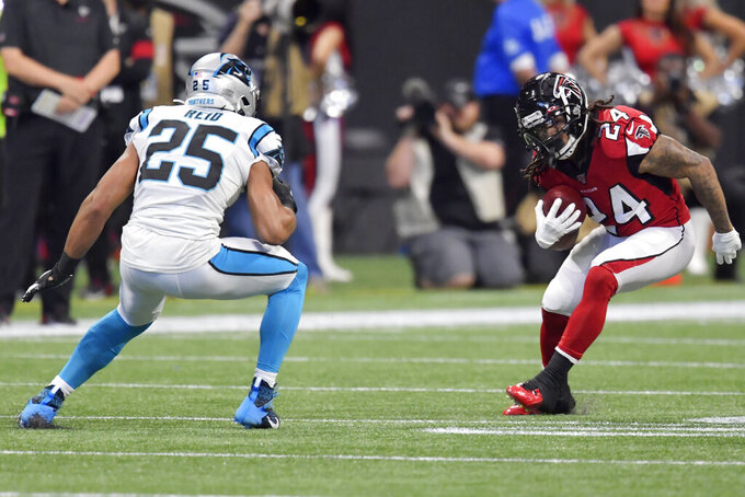 Atlanta Falcons running back Devonta Freeman (24) runs against Carolina Panthers strong safety Eric Reid (25) during the first half of an NFL football game, Sunday, Dec. 8, 2019, in Atlanta. (AP Photo/Mike Stewart)