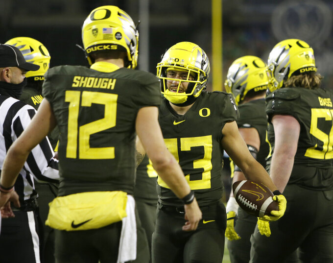 Oregon quarterback Tyler Shough, left, celebrates with Cyrus Habibi-Likio, center, after a fourth quarter touchdown during an NCAA college football game Saturday, Nov. 7, 2020, in Eugene, Ore. (AP Photo/Chris Pietsch)