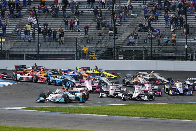 Colton Herta leads the field through the first turn on the start of an IndyCar auto race at Indianapolis Motor Speedway in Indianapolis, Friday, Oct. 2, 2020. (AP Photo/Michael Conroy)