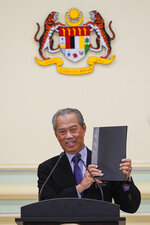 Malaysian Prime Minister Muhyiddin Yassin shows a list of his cabinet ministers during a press conference at his office in Putrajaya, Malaysia, Monday, on March 9, 2020. A key ally has reaffirmed support for Malaysian Prime Minister Muhyiddin Yassin's government, offering him a respite after his failed bid to declare a coronavirus emergency,  but his political survival still hangs in the balance.  (AP Photo/Vincent Thian)