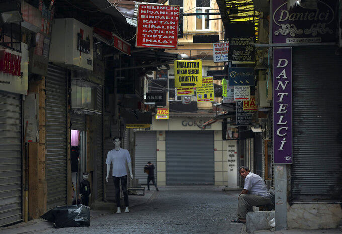 """A vendor waits for customers in Eminonu market, an area usually packed with shop goers, but currently nearly deserted due to the strict lockdown to help curb the spread of the coronavirus, in Istanbul, Saturday, May 8, 2021. The """"full lockdown,"""" which began in late April and will last until May 17 came amid a huge surge in infections. (AP Photo/Emrah Gurel)"""