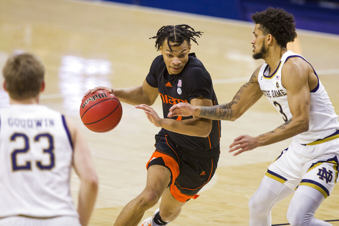 Miami's Isaiah Wong, center, drives between Notre Dame's Dane Goodwin (23) and Prentiss Hubb (3) during the first half of an NCAA college basketball game Sunday, Feb. 14, 2021, in South Bend, Ind. (AP Photo/Robert Franklin)