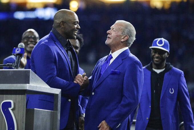 Former Indianapolis Colts defensive end Dwight Freeney shakes hands with Colts owner Jim Irsay during his Ring of Honor induction ceremony during half time of an NFL football game against the Miami Dolphins in Indianapolis, Sunday, Nov. 10, 2019. (AP Photo/Darron Cummings)
