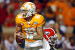 Tennessee quarterback Brian Maurer (18) outruns a Georgia defender in the second half of an NCAA college football game, Saturday, Oct. 5, 2019, in Knoxville, Tenn. (AP Photo/Wade Payne)