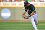 Louisville second baseman Justin Lavey bobbles a ball hit for a base hit by Vanderbilt's Austin Martin during the sixth inning of an NCAA College World Series baseball game in Omaha, Neb., Friday, June 21, 2019. (AP Photo/Nati Harnik)