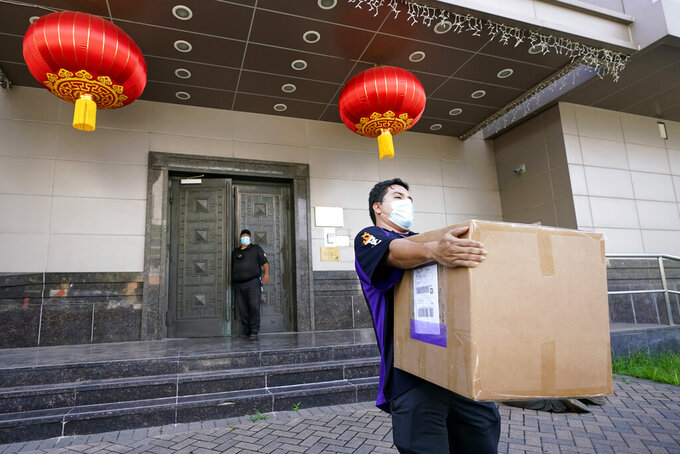 """A FedEx employee removes a box from the Chinese Consulate Thursday, July 23, 2020, in Houston. China says """"malicious slander"""" is behind an order by the U.S. government to close its consulate in Houston,  and maintains that its officials have never operated outside ordinary diplomatic norms. (AP Photo/David J. Phillip)"""