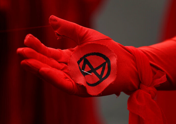 FILE - In this file photo dated Wednesday, Oct. 9, 2019, an Extinction Rebellion logo is seen on the gloved hand of a climate change protester in London.  A co-founder of British environmental activist Extinction Rebellion group, Roger Hallam has sparked anger in Germany after appearing to downplay the Holocaust in an interview with German newspaper Die Zeit released Wednesday Nov. 20, 2019. (AP Photo/Matt Dunham, FILE)