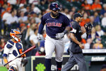 Cleveland Indians designated hitter Franmil Reyes, middle, flips his bat in front of Houston Astros catcher Martin Maldonado, left, and umpire Edwin Moscoso, right, after his home run against the Houston Astros during the fourth inning of a baseball game Monday, July 19, 2021, in Houston. (AP Photo/Michael Wyke)