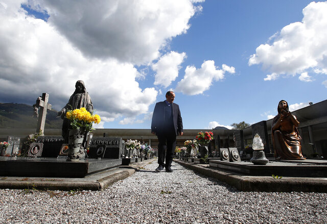 Rev. Mario Carminati walks in a cemetery in Casnigo, near Bergamo, Italy, Sunday, Sept. 27, 2020. As the world counts more than 1 million COVID victims, the quiet of everyday life and hum of industry has returned to Bergamo, which along with the surrounding Lombardy region was the onetime epicenter of the outbreak in Europe. But the memory of those dark winter days, and the monumental toll of dead they left behind, has remained with those who survived only to see the rest of the world fall victim, too. (AP Photo/Antonio Calanni)