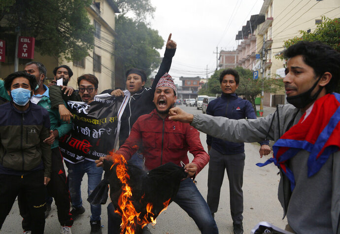 FILE - In this Monday, May 11, 2020, file photo, Nepalese students shout slogans during a protest against the Indian government inaugurating a new road through a disputed territory between India and Nepal, in Kathmandu, Nepal. Nepal's latest border dispute with India, that has strained relations between the two South Asian countries with centuries-old historical, cultural and economical ties, has brought tiny Himalayan nation's bickering political parties together in a rare show of unity. (AP Photo/Niranjan Shrestha, File)