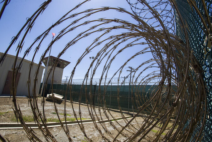 FILE - In this Wednesday, April 17, 2019 file photo reviewed by U.S. military officials, the control tower is seen through the razor wire inside the Camp VI detention facility in Guantanamo Bay Naval Base, Cuba. A plan to offer the COVID-19 vaccine to prisoners at the Guantanamo Bay detention center, which was halted earlier in 2021 amid a political backlash, is on again as health authorities on April 19, 2021 expanded the vaccination program on the Navy base in Cuba to the entire adult population of the remote facility. (AP Photo/Alex Brandon, File)