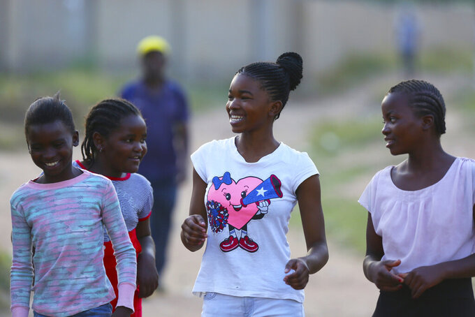 Natsiraishe Maritsa, center, shares a light moment with young boys and girls after a taekwondo training session in the Epworth settlement about 15 km southeast of the capital Harare, Saturday Nov. 7, 2020. In Zimbabwe, where girls as young as 10 are forced to marry due to poverty or traditional and religious practices, a teenage martial arts fan 17-year old Natsiraishe Maritsa is using the sport to give girls in an impoverished community a fighting chance at life. (AP Photo/Tsvangirayi Mukwazhi)