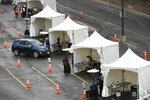 Cars line up individually in front of COVID-19 vaccination stations in the parking lots of Coors Field on Sunday, Jan. 24, 2021, in Denver, Colo.  (Helen H. Richardson/The Denver Post via AP)