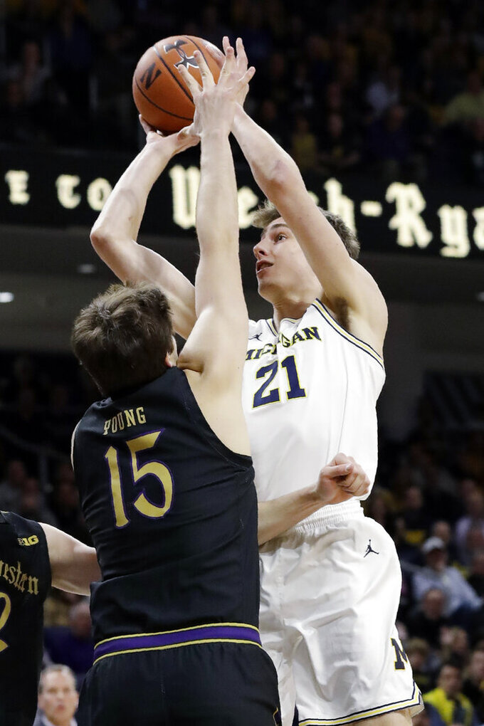 Michigan guard Franz Wagner, right, shoots against Northwestern center Ryan Young during the first half of an NCAA college basketball game in Evanston, Ill., Wednesday, Feb. 12, 2020. (AP Photo/Nam Y. Huh)
