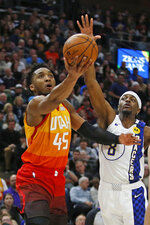 Utah Jazz guard Donovan Mitchell (45) lays the ball up as Indiana Pacers forward Justin Holiday (8) defends in the second half of an NBA basketball game Monday, Jan. 20, 2020, in Salt Lake City. (AP Photo/Rick Bowmer)