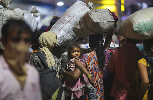 FILE - In this Saturday, May 23, 2020, file photo, migrant workers line up to board trains to their home states at a railway station in Hyderabad, India. The head of India's massive railway system said Friday, May 29, that authorities are investigating whether some migrant workers died of starvation or sickness this week while traveling on special trains to their home villages in blazing heat after losing their jobs in cities because of the coronavirus lockdown. Railway Board Chairman Vinod Kumar Yadav said more than 5 million migrant workers and their families this month from cities and towns to their home villages on 3,840 trains. (AP Photo/Mahesh Kumar A., File)