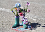 In this photo taken on Wednesday, May 15, 2019, flowers in boots are pictured in a no parking zone on the environmental island Langeoog in the North Sea, Germany. Concerns about climate change have prompted mass protests across Europe for the past year and are expected to draw tens of thousands onto the streets again Friday, May 24. For the first time, the issue is predicted to have a significant impact on this week's elections for the European Parliament. (AP Photo/Martin Meissner)