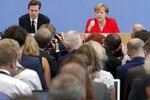 German Chancellor Angela Merkel, rear right, addresses the media during her annual sommer press conference in Berlin, Germany, Friday, July 19, 2019. (AP Photo/Michael Sohn)