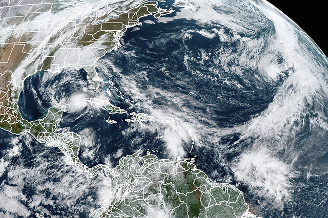 This Tuesday, Nov. 10, 2020, satellite image made available by NOAA shows Tropical Storm Eta at 10:40 a.m. EST in the Gulf of Mexico, Theta, right, and a tropical wave to the south that forecasters say has a good chance of becoming Tropical Storm Iota. (NOAA via AP)