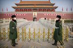 Los guardias con máscaras sanitarias en la Puerta Tiananmen, cerca de la Plaza Tiananmen, en Beijing, el 27 de enero del 2020. (AP Photo/Mark Schiefelbein)