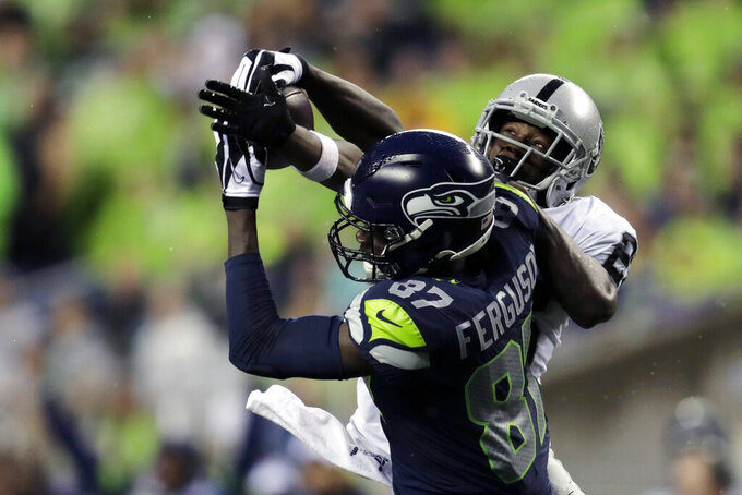 Seattle Seahawks wide receiver Jazz Ferguson (87) makes a 41-yard catch around the defense of Oakland Raiders cornerback Nevin Lawson, right, during the first half of an NFL football preseason game Thursday, Aug. 29, 2019, in Seattle. (AP Photo/Stephen Brashear)