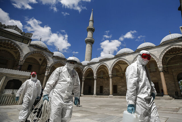Municipality workers disinfect the grounds of the historical Suleymaniye Mosque, in Istanbul, during the third day of Eid el-Fitr and the last day of a four-day curfew due to the coronavirus outbreak, Tuesday, May 26, 2020. Istanbul's municipality workers disinfected several mosques which were locked down for more than six weeks and will be partly open again for prayers on Friday, May 29. The Muslim holiday marking the end of the fasting month of Ramadan, traditionally a time of gathering, was marked by a nationwide lockdown to combat the coronavirus. (AP Photo/Emrah Gurel)