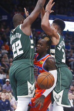 Oklahoma City Thunder guard Dennis Schroeder, center, loses the ball as he is defended by Milwaukee Bucks forwards Khris Middleton (22) and Giannis Antetokounmpo (34) during the first half of an NBA basketball game Sunday, Nov. 10, 2019, in Oklahoma City. (AP Photo/Sue Ogrocki)