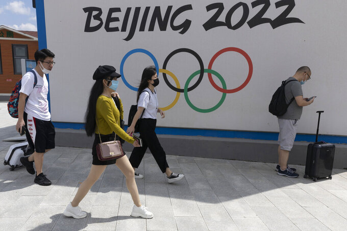Visitors to Chongli, one of the venues for the Beijing 2022 Winter Olympics, pass by the Olympics logo in Chongli in northern China's Hebei Province on Aug. 13, 2020. The coronavirus's delta variant is challenging China's costly strategy of isolating cities, prompting warnings that Chinese leaders who were confident they could keep the virus out of the country need a less disruptive approach. China's controls will be tested when thousands of athletes, reporters and others arrive for the Winter Olympics in Beijing in February.  (AP Photo/Ng Han Guan)
