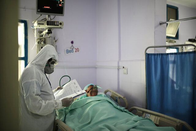 A medical worker wearing personal protective equipment takes care of a COVID-19 patient in an intensive care unit at a hospital in Sanaa, Yemen, Sunday, June 14, 2020. (AP Photo/Hani Mohammed)