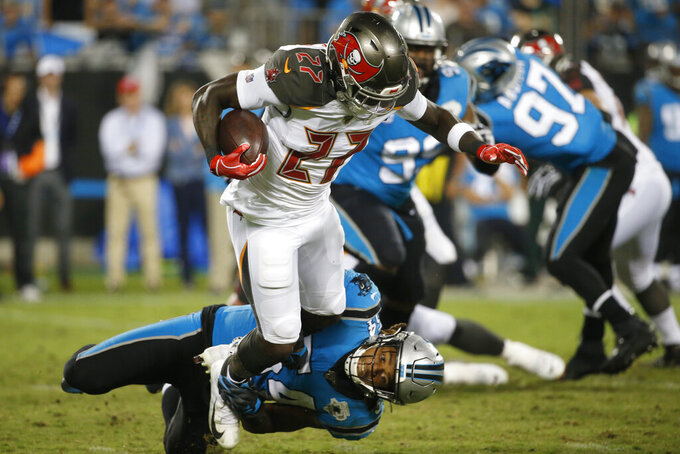 Tampa Bay Buccaneers running back Ronald Jones (27) is tackled by Carolina Panthers outside linebacker Shaq Thompson (54) during the second half of an NFL football game in Charlotte, N.C., Thursday, Sept. 12, 2019. (AP Photo/Brian Blanco)
