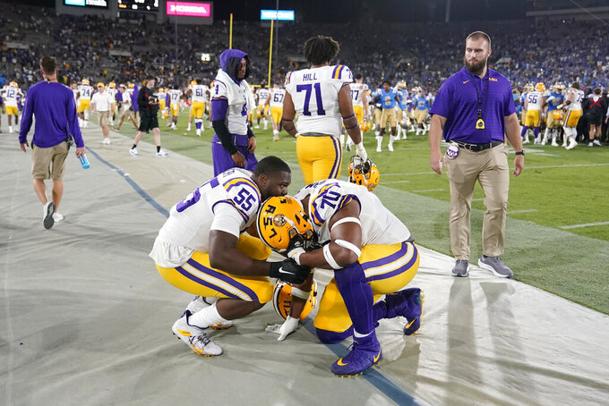 LSU guard Ed Ingram (70) is consoled by offensive lineman Kimo Makane'ole (55) after the team's loss to UCLA in an NCAA college football game Saturday, Sept. 4, 2021, in Pasadena, Calif. (AP Photo/Marcio Jose Sanchez)