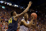 Kansas' David McCormack (33) shoots under pressure from West Virginia's Oscar Tshiebwe (34) during the first half of an NCAA college basketball game Saturday, Jan. 4, 2020, in Lawrence, Kan. (AP Photo/Charlie Riedel)
