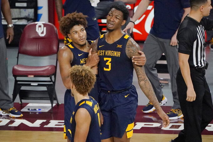 West Virginia forward Gabe Osabuohien (3) reacts after being called for a foul late in the second half of an NCAA college basketball game against Oklahoma, Saturday, Jan. 2, 2021, in Norman, Okla. West Virginia guard Miles McBride is at left. AP Photo/Sue Ogrocki)