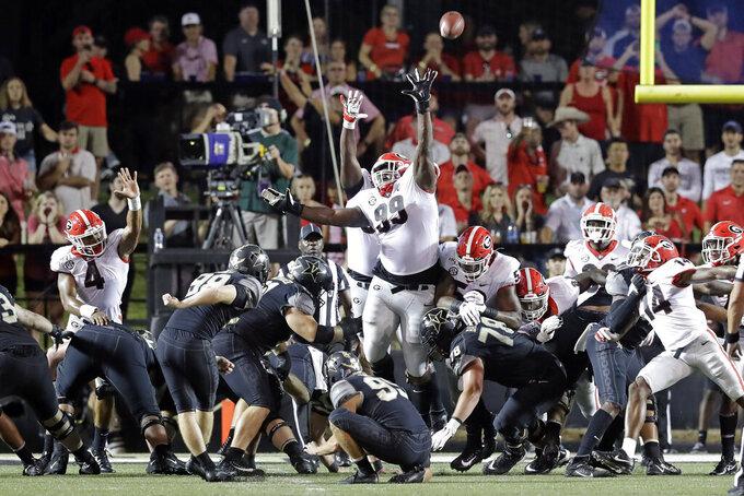 Georgia defensive lineman Jordan Davis (99) reaches for a 26-yard field goal by Vanderbilt kicker Ryley Guay (98) in the first half of an NCAA college football game Saturday, Aug. 31, 2019, in Nashville, Tenn. (AP Photo/Mark Humphrey)