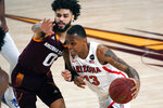 Arizona guard James Akinjo (13) drives on Arizona State guard Holland Woods during the second half of an NCAA college basketball game, Thursday, Jan. 21, 2021, in Tempe, Ariz. Arizona won 84-82. (AP Photo/Rick Scuteri)