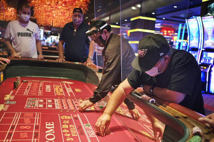 Craps players and dealers are seperated by partitions at the Golden Nugget Casino in Atlantic City, N.J., Thursday, July 2, 2020. Eager to hit the slot machines and table games after a 108-day absence, gamblers wore face masks and did without smoking and drinking Thursday as Atlantic City's casinos reopened amid the coronavirus pandemic that has drastically changed things both inside and outside the casino walls. (AP Photo/Seth Wenig)