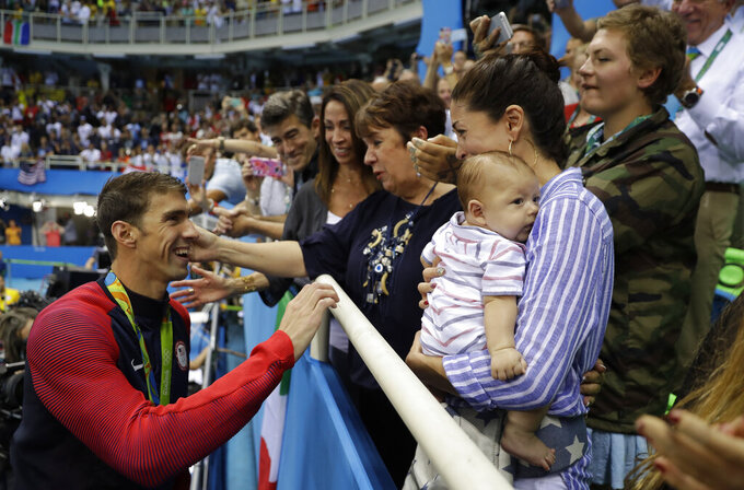 FILE - In this Tuesday, Aug. 9, 2016, file photo, United States' Michael Phelps celebrates winning his gold medal in the men's 200-meter butterfly with his mother Debbie, fiance Nicole Johnson and baby Boomer during the swimming competitions at the 2016 Summer Olympics in Rio de Janeiro, Brazil. Private, touching moment between loved ones won't be happening at the pandemic-delayed Tokyo Olympics. No spectators — local or foreign — will be allowed at the majority of venues, where athletes will hang medals around their own necks to protect against spreading the coronavirus. No handshakes or hugs on the podium, either. (AP Photo/Matt Slocum, File)