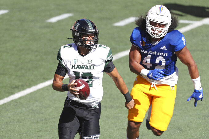 San Jose State defensive end Viliami Fehoko (42) chases Hawaii quarterback Chevan Cordeiro (12) in the first half of an NCAA college football game Saturday, Dec. 5, 2020, in Honolulu. (AP Photo/Marco Garcia)