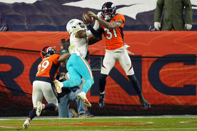 Denver Broncos free safety Justin Simmons (31) intercepts a pass in the end zone intended for Miami Dolphins wide receiver DeVante Parker (11) during the second half of an NFL football game, Sunday, Nov. 22, 2020, in Denver. The Broncos won 20-13. (AP Photo/Jack Dempsey)