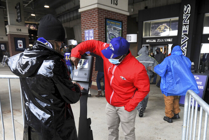 A fan is instructed on how to scan a game ticker prior to an NFL football game between the Baltimore Ravens and the Pittsburgh Steelers, Sunday, Nov. 1, 2020, in Baltimore. A limited number of fans were allowed to attend the game at M&T Bank Stadium for the first time during the season under COVID-19 restrictions. (AP Photo/Gail Burton)